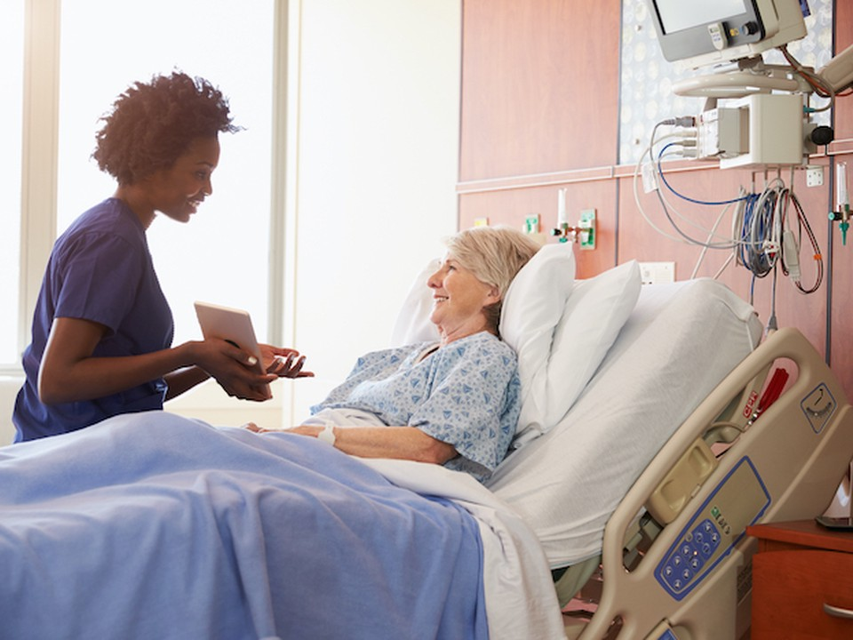 Hospital Nurse With Digital Tablet Talks To Senior Patient